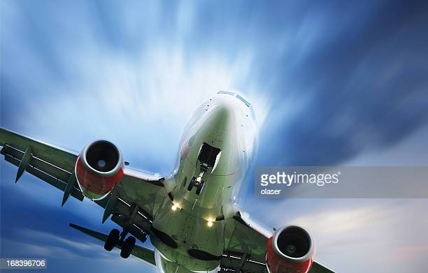Sunlit airplane taking off against dramatic sky