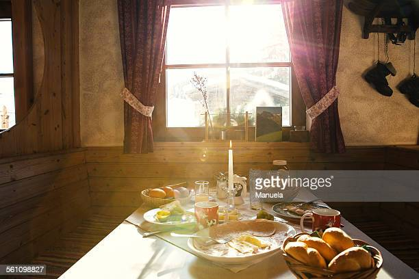 Sunlit breakfast table in log cabin
