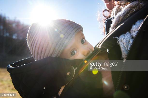 Sunlit close up of baby boy wearing knit hat, carried in baby sling by mother