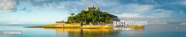 sunlit island in tranquil sea st michaels mount panorama cornwall - panoramic stock pictures, royalty-free photos & images