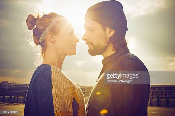 sunlit portrait of mid adult couple face to face on rooftop parking lot - angesicht zu angesicht stock-fotos und bilder