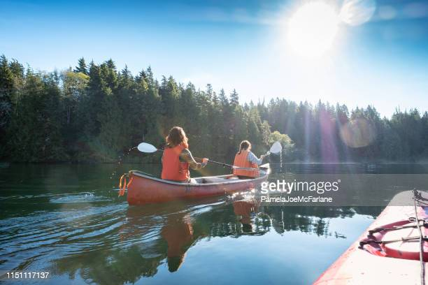 pov, sunlit summer kayaking with women canoeing in wilderness inlet - kayak stock pictures, royalty-free photos & images