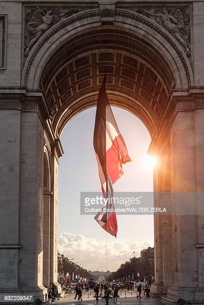Sunlit view of french flag and Arc de Triomphe, Paris, France