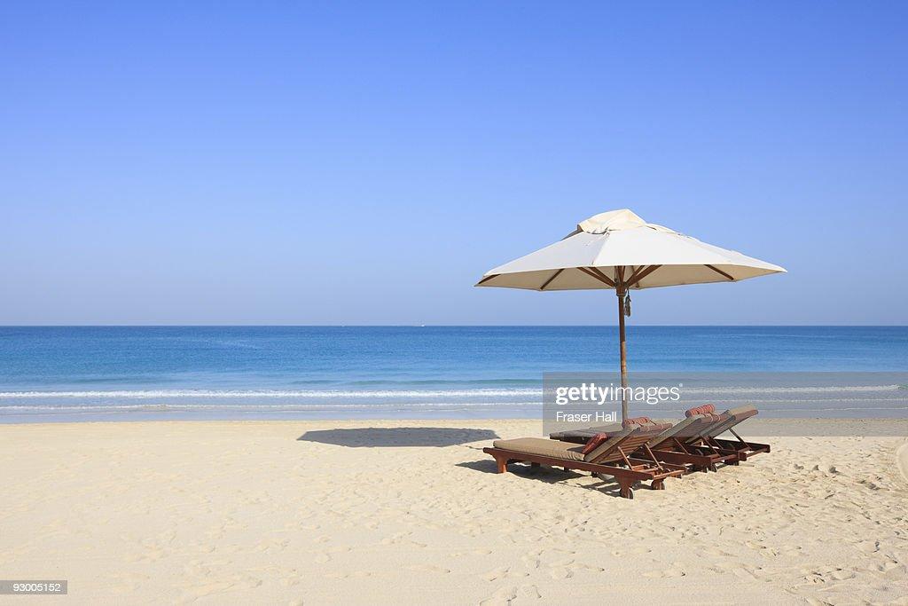 Sunlounger and umbrella on an empty beach : Stock Photo
