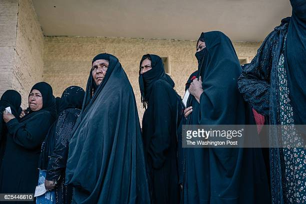 Sunni Arabs recebtly displaced stand outside a center for screening and registration of newly displaced civilians outside Tikrit Several families...