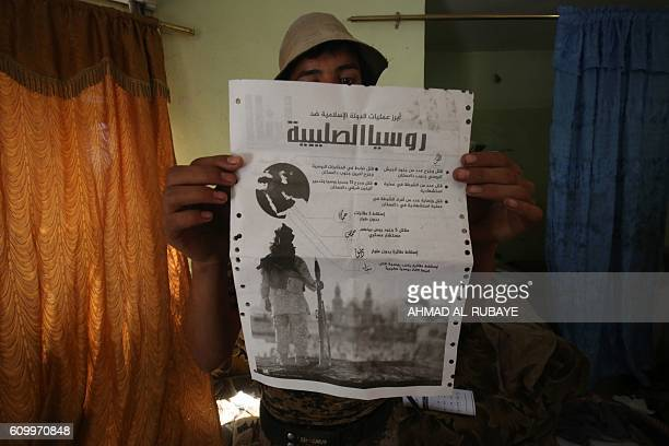 A Sunni fighter from the Popular Mobilisation Units supporting the government forces holds up a document he found in a building in the town of...