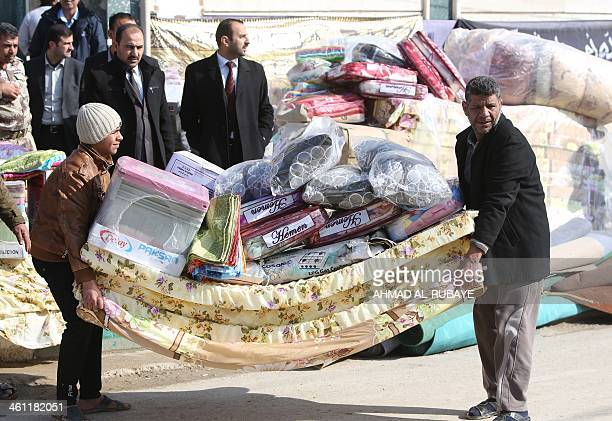 Sunni Muslim Iraqis who fled Fallujah with their families carry blankets and mattresses distributed by the International Organization for Migration...