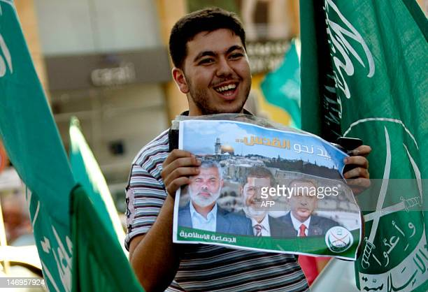 A Sunni Muslim man supporter of the Jamaat alIslamiyah holds a poster with the images of Islamist Hamas leader Ismail Haniya newly elected Egyptian...