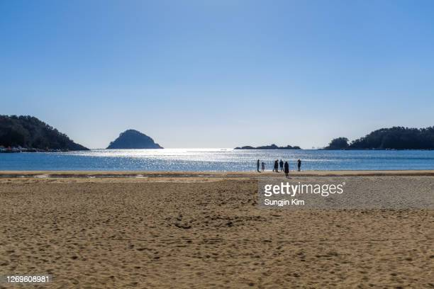 sunny beach with island - sungjin kim stock pictures, royalty-free photos & images