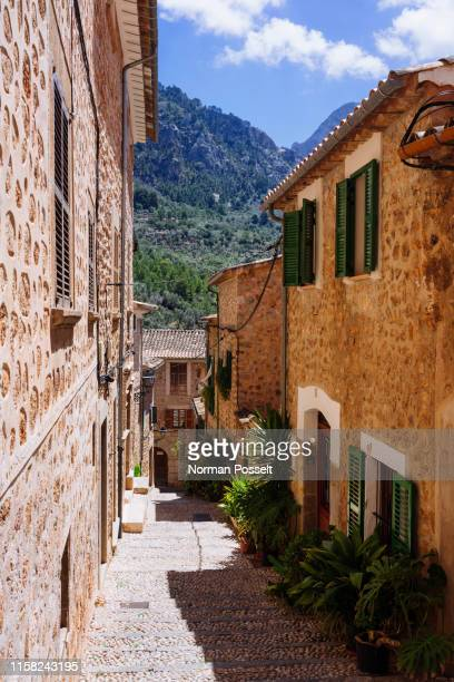 sunny cobblestone street and houses, fornalutx, mallorca, balearic islands, spain - stone house stock pictures, royalty-free photos & images