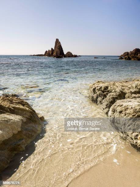 Sunny day on the beach and rocky coast of the Cabo de Gata with formations of volcanic rock. Cabo de Gata - Nijar Natural Park, Sirens reef, Beach, Biosphere Reserve, Almeria,  Andalusia, Spain