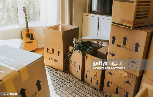 a sunny domestic room full of stacked cardboard boxes during the relocation process - absence stock pictures, royalty-free photos & images