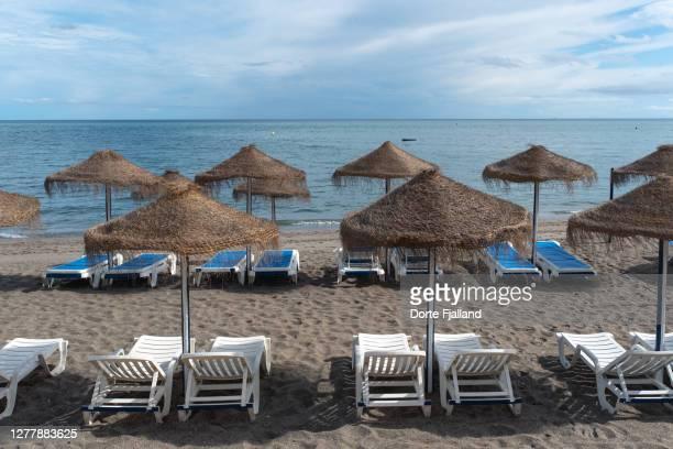 sunny, empty beach with parasols and lounge chairs - dorte fjalland fotografías e imágenes de stock