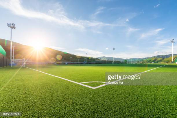 sunny football field at sunset - voetbalveld stockfoto's en -beelden