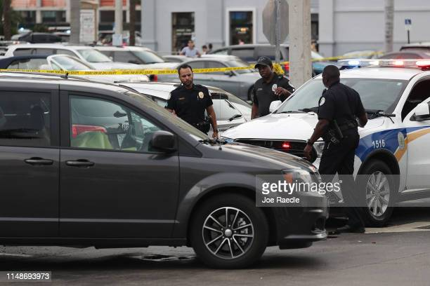 Sunny Isles Beach police officers stand near a van where an individual was found shot to death after a shooting close by that reports say involved...