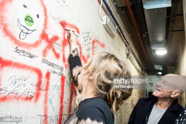 Sunny Ozell writes her name on an artist graffiti wall as husband Patrick Stewart watches on backstage at the launch of AmericanaFest UK at The...