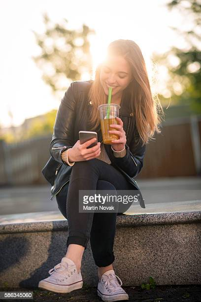 Sunny relax - teen with phone and drink