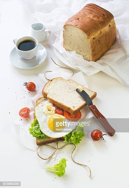 Sunny side up egg sandwich and espresso on white dinning table top. Close-up overhead view.