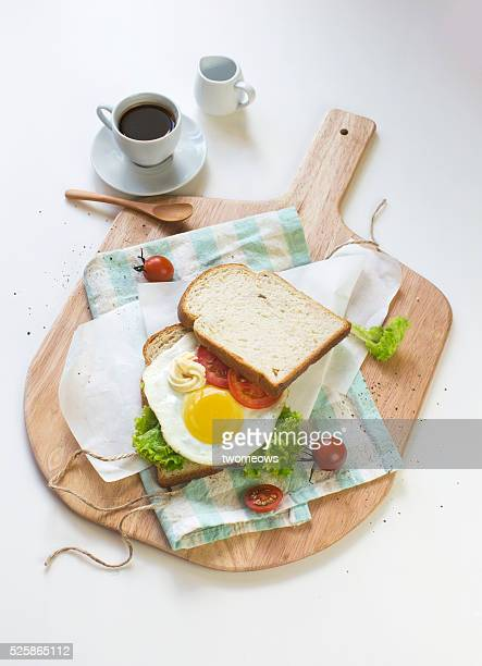Sunny side up sandwich and espresso on white dinning table top. Close-up overhead view.