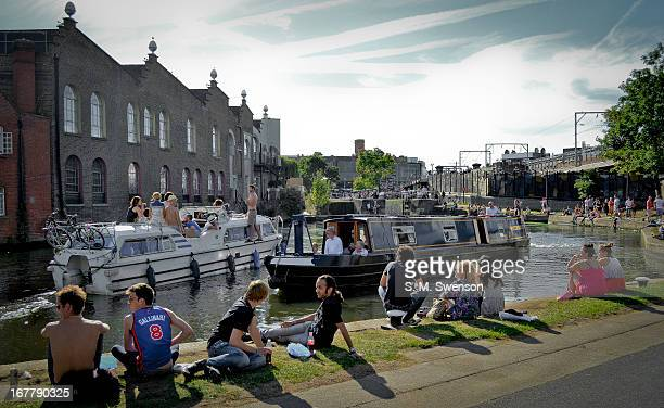 Sunny warm summer's day along Regent's Canal in Camden, North London. There are many young people sitting on the edge watching barges and boats go by...