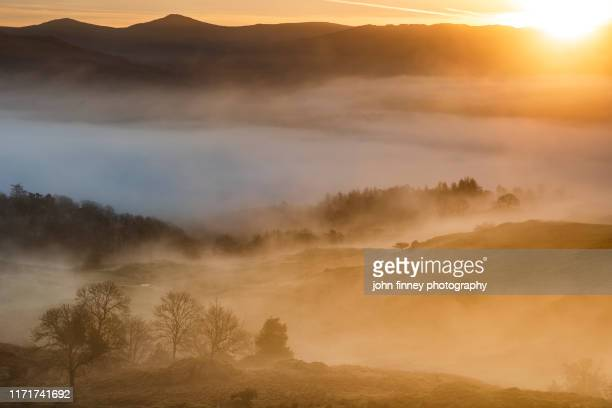 sunrise above fog with a lake district landscape, uk. - dramatic landscape stock pictures, royalty-free photos & images