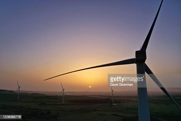 Sunrise aerial view of new wind turbines constructed between vineyards and fruit orchards as part of the Valley of Tears wind turbines farm project...