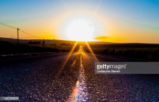 sunrise align with the road stripes (read line markings) so well in r614 to wartburg, south africa - pietermaritzburg stock pictures, royalty-free photos & images