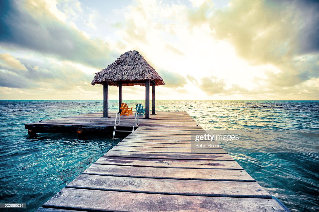 Sunrise at a pier near a resort on a Caribbean island in Belize : Stock Photo