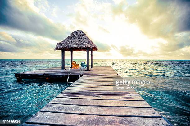 sunrise at a pier near a resort on a caribbean island in belize - robb reece stock pictures, royalty-free photos & images