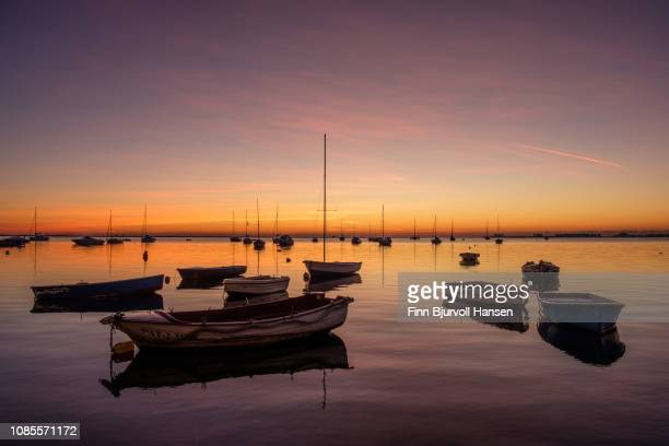 sunrise at mar menor spain - boats in the forground - finn bjurvoll stock photos and pictures