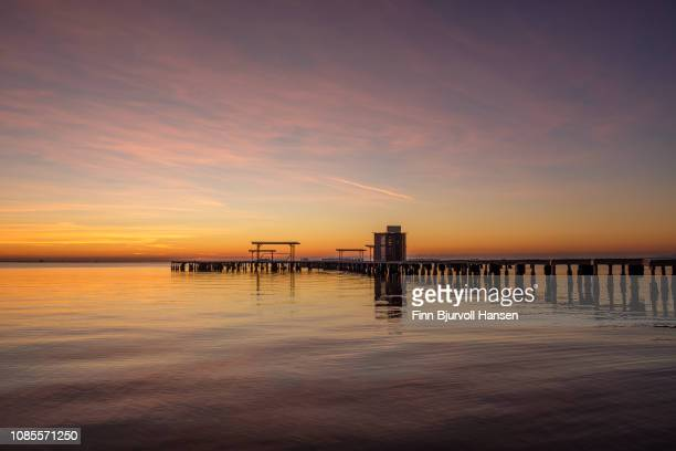 sunrise at mar menor spain with la manga i the horizon - water and pier right side - finn bjurvoll stock photos and pictures
