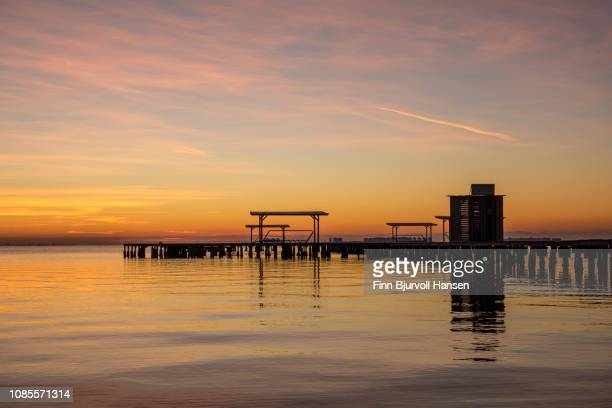 sunrise at mar menor spain with la manga i the horizon - water and pier left side - finn bjurvoll stock photos and pictures