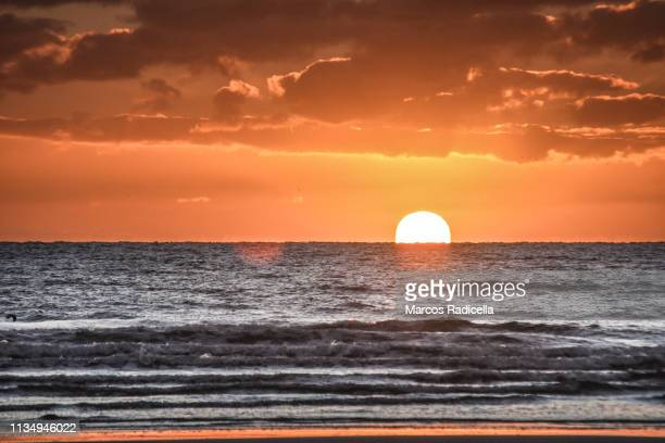 sunrise at patagonian shore - radicella stock photos and pictures