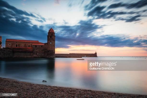 """sunrise at """"plage des pêcheurs"""" in front of """"église notre-dame des anges"""" of collioure, france - collioure photos et images de collection"""