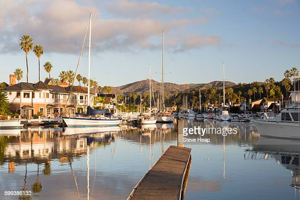 Sunrise at residential development of modern homes and boats by water in Ventura, California, USA