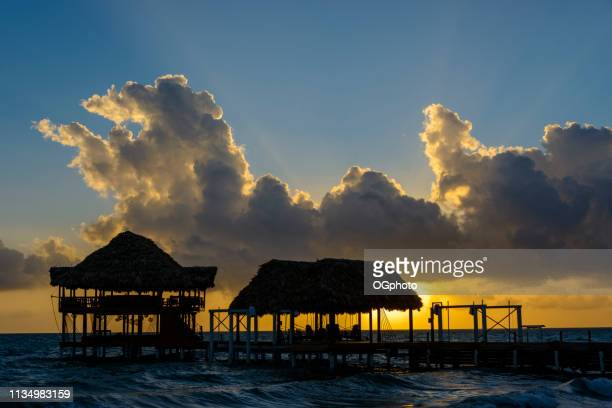 sunrise at the beach with silhouette of pier with thatched huts - ogphoto stock pictures, royalty-free photos & images