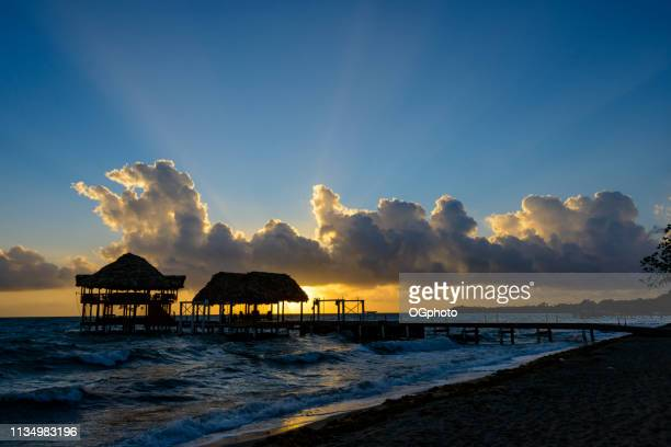 Sunrise at the beach with silhouette of pier with thatched huts