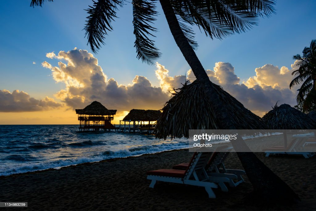 Sunrise at the beach with silhouette of pier with thatched huts : Stock Photo