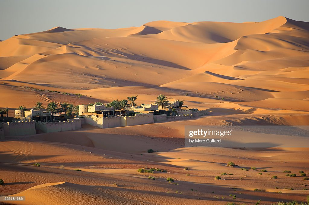 Sunrise at the Qasr Al-Sarab desert resort near Liwa, United Arab Emirates. The luxury resort is nestled in the dunes of the Empty Quarter - a part of the Arabian Desert which covers much of the peninsula. : Stock Photo