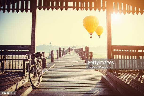sunrise at u bein bridge with hot air balloon, mandalay, myanmar - myanmar culture stock photos and pictures