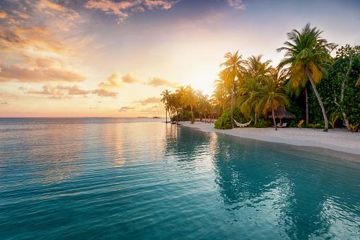 Sunrise behind a tropical island in the Maldives 1151755587
