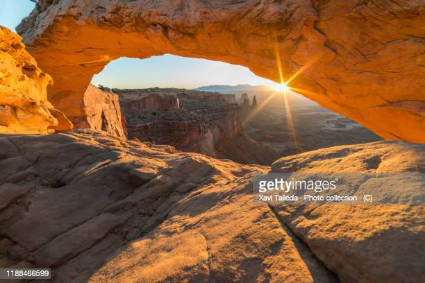 sunrise behind mesa arch in canyonlands - mesa arch stock pictures, royalty-free photos & images