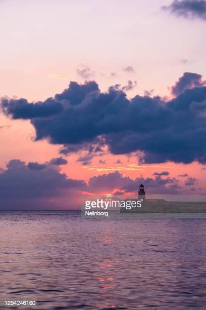 beautiful sunrise behind lighthouse grand harbor