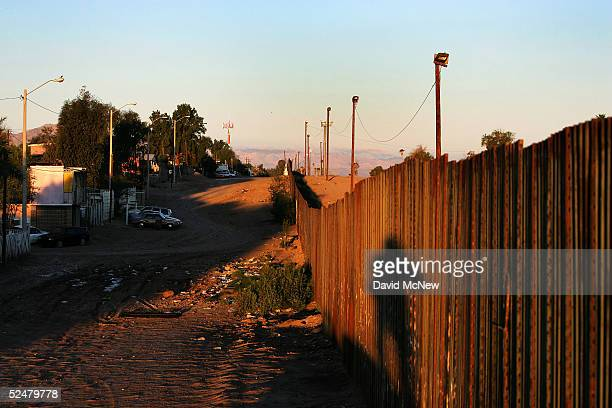Sunrise casts the shadow on the Mexico side of the USMexico border fence March 25 2005 between Mexicali Mexico and Calexico California Since the...