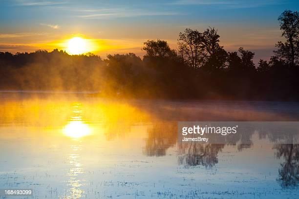 Sunrise Explodes Over Steamy Lake