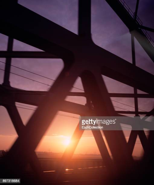 Sunrise from moving train, passing railroad bridge