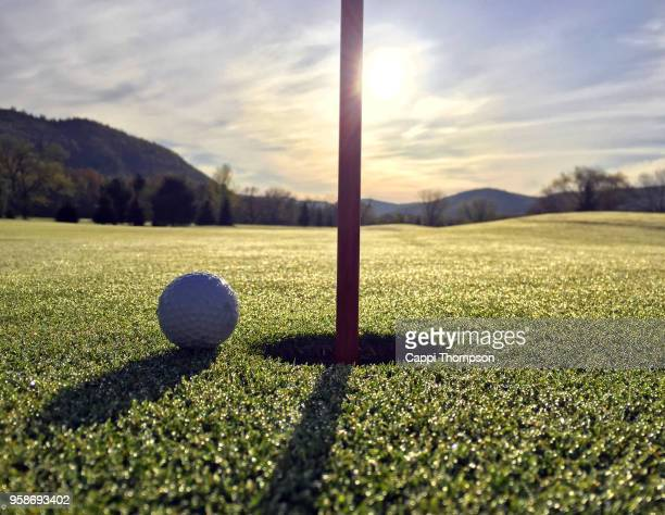 sunrise golf ball resting near cup - golf flag stock photos and pictures