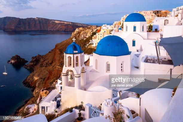 sunrise, iconic blue and white chapels, oia, santorini, greece - kuppel stock-fotos und bilder