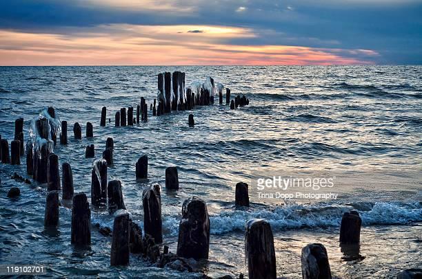 sunrise & icy pilings,  lake michigan, illinois - evanston illinois stock photos and pictures
