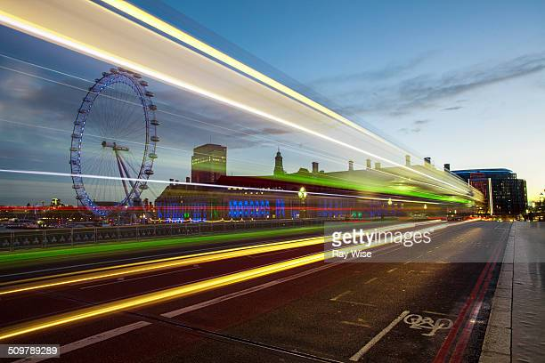 Sunrise in London and the famous Millennium Wheel is positioned behind flowing traffic to give light beam affects over a long exposure